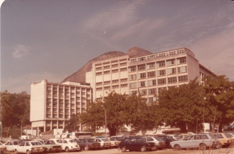 Vista a partir do estacionamento para o Edifício Cardeal Leme e a Ala Frings do Edifício da Amizade. 1985. Fotógrafo Antônio Albuquerque. Acervo da Vice-Reitoria de Desenvolvimento.