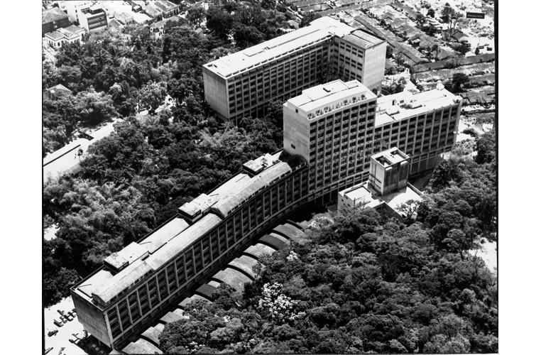 Vista aérea do campus Gávea, com o ITUC, o laboratório Van de Graaff, o Edifício Cardeal Leme, o antigo ginásio esportivo, o Edifício da Amizade e ao fundo, à direita, o Parque Proletário da Gávea. c. 1974. Fotógrafo desconhecido. Acervo Núcleo de Memória.