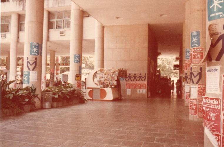 Na entrada da Ala Frings, paredes cobertas com propagandas do movimento estudantil na PUC-Rio. Ao centro a banca de jornal que ficava onde atualmente há um caixa eletrônico. 1985. Fotógrafo desconhecido. Acervo do Projeto Comunicar.