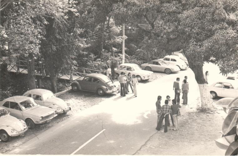 Vista da via de passagem principal da PUC-Rio e da primeira ponte de acesso ao Edifício da Amizade, com alunos e carros. 1980. Fotógrafo Antônio Albuquerque. Acervo da Vice-Reitoria de Desenvolvimento.