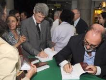 À direita, o prof. Hilton Koch escreve dedicatória no livro durante o evento. Fotógrafo Antônio Albuquerque. Acervo do Núcleo de Memória.