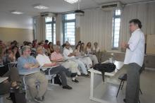 O Prof. Eduardo Jardim apresenta o palestrante na sala F502. Sentados na primeira fila à esquerda o Prof. Ricardo Benzaquen e o palestrante Prof. Eduardo Jardim. Fotógrafo Antônio Albuquerque. Acervo do Núcleo de Memória.