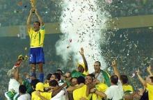 Cafu, o capitão do time brasileiro, ergue o troféu entregue ao time  vencedor ao final do jogo Brasil - Alemanha.