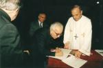 O Pe. Pedro assina o termo de Lançamento da Pedra Fundamental da Igreja do Sagrado Coração de Jesus. 2000. Fotógrafo desconhecido.